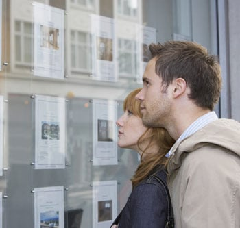 Couple looks at real estate listings in a window