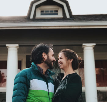 Smiling couple in front of a home