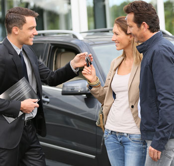 Couple at car dealer taking keys