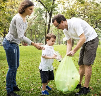 Family picking up litter in the park