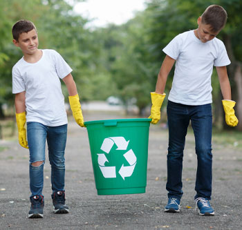Two kids carrying a recycling bin