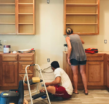 Couple installing kitchen cabinets