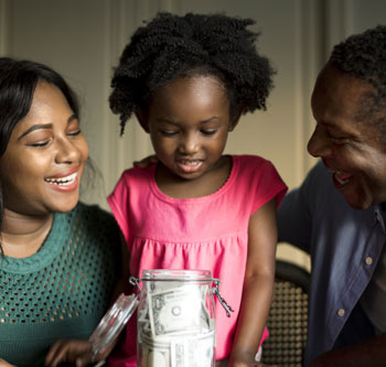 Mom, dad, and daughter looking at money in a jar
