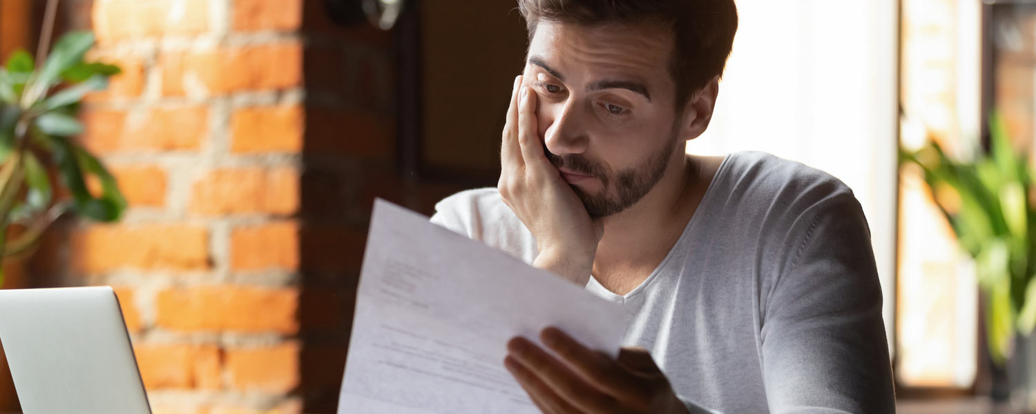 Confused man looks at his credit card statement