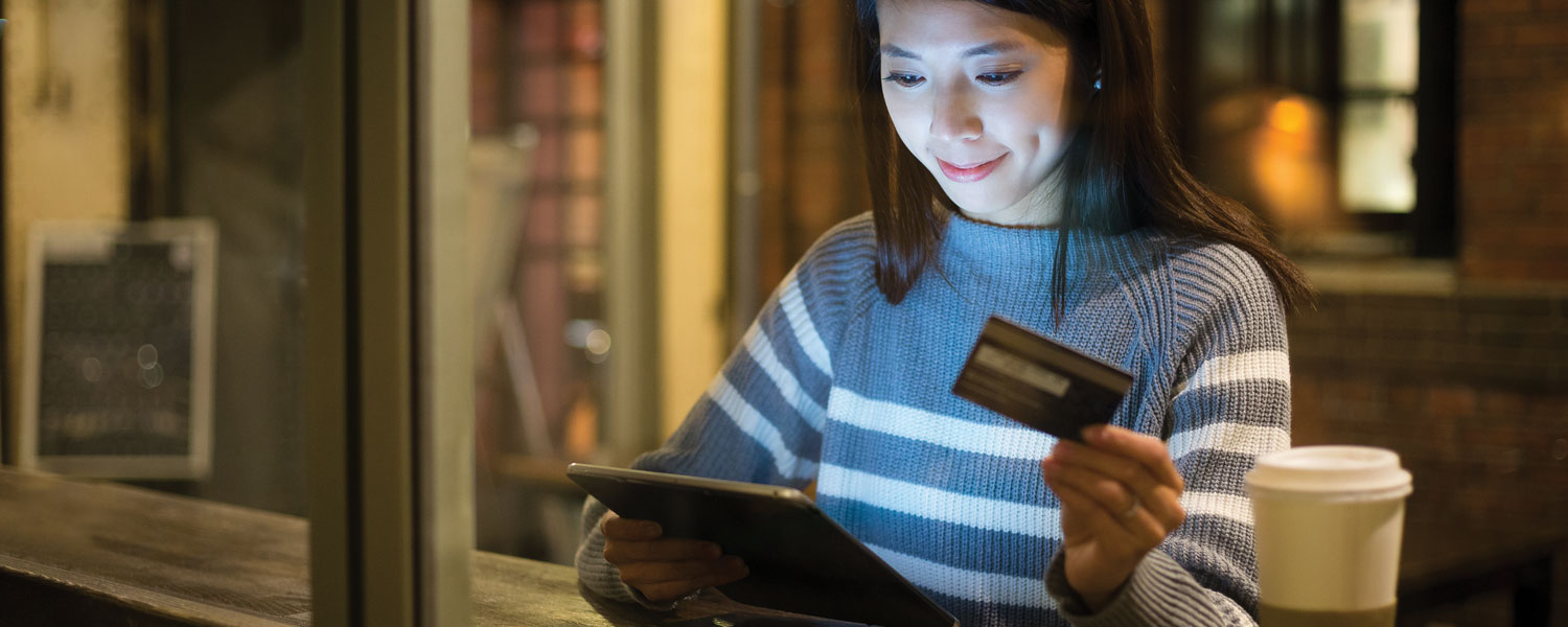 Woman using credit card to buy something on her tablet