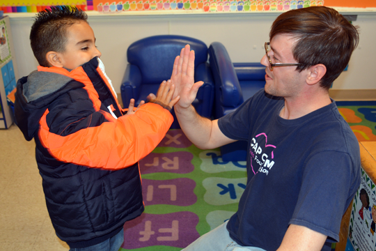 CAP COM volunteering high-fiving with child during Coats for Kids delivery day