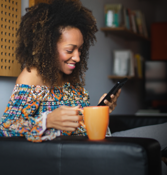 A black woman sitting on her couch using her cell phone while drinking coffee