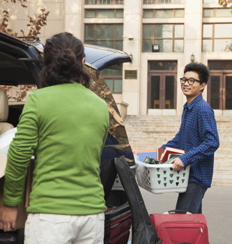 An Asian student unpacking a car with his mom in front of his college dorm.