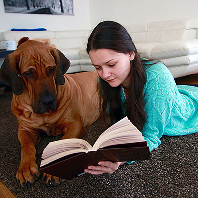 A girl reading a book with her dog.